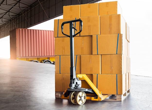 Skrzynki transportowe, ciężarówka towarowa, pudła towarowe na palecie czekające na załadowanie do kontenera transportowego.