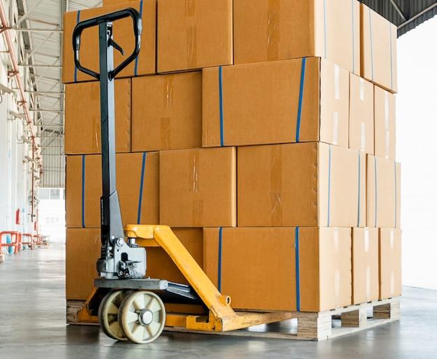 Skrzynki transportowe, ręczny wózek paletowy i stos pudełek opakowaniowych na palecie w magazynie.