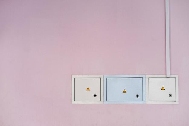 Skrzynki zasilaczy w różowej ścianie.