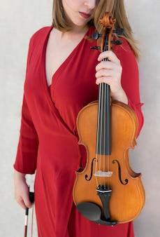Skrzypaczka pozuje podczas gdy trzymający skrzypce