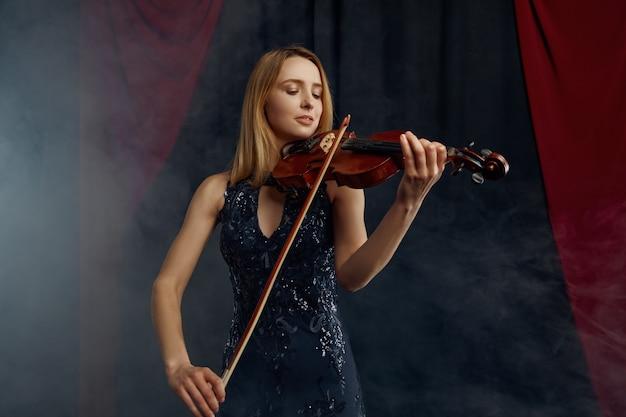 Skrzypaczka żeńska z smyczkiem i skrzypcami, koncert solowy na scenie. kobieta ze strunowym instrumentem muzycznym, muzyk gra na altówce
