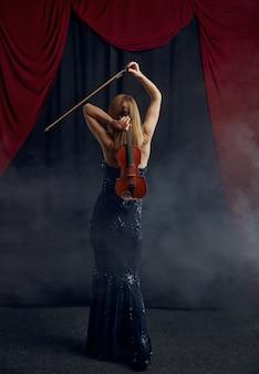 Skrzypaczka żeńska ze smyczkiem i skrzypcami za plecami, wirtuozowski występ na scenie. kobieta ze strunowym instrumentem muzycznym, sztuka muzyczna, muzyk gra na altówce