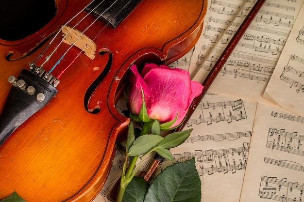Skrzypce, czerwona róża i nuty.