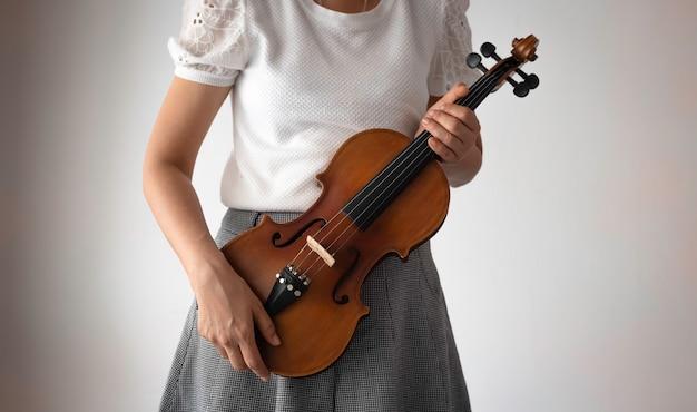 Skrzypce trzymane ludzką ręką, pokazują szczegóły instrumentu akustycznego, rozmyte światło dookoła