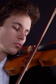 Skrzypek grający na skrzypcach z zamkniętymi oczami