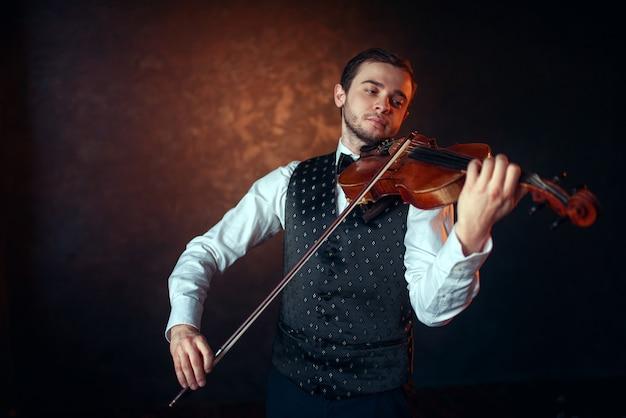 Skrzypek męski grający muzykę klasyczną na skrzypcach