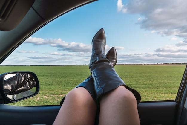 Skrzyżowane nogi kaukaskiej kobiety w kowbojskich butach przez okno samochodu, słoneczny dzień z chmurami
