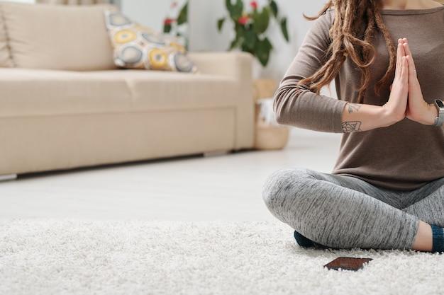 Skrzyżowane nogi młodej aktywnej kobiety trzymającej ręce razem za klatkę piersiową siedząc na podłodze w domu