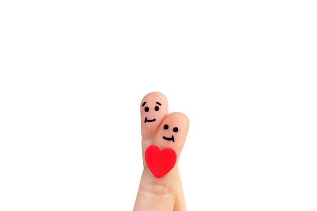 Skrzyżowane palce z radosną buźką i czerwonym sercem na białym tle