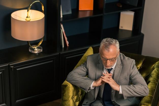 Skrzyżowane palce. zamyślony poważny siwy mężczyzna siedzi ze skrzyżowanymi palcami w fotelu i patrzy w dół