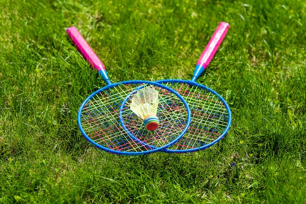 Skrzyżowane rakiety do badmintona z lotką nad nim na trawie
