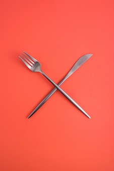 Skrzyżowane widelce i nóż na pomarańczowym tle, symbol cateringu, kawiarni, restauracji.