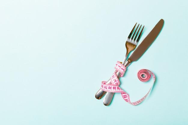 Skrzyżowane widelec i nóż są owinięte taśmą mierniczą