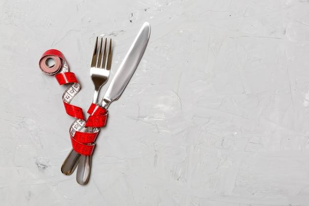 Skrzyżowane widelec i nóż są owinięte taśmą pomiarową na szarym tle. pojęcie diety dla odchudzania z kopii przestrzenią