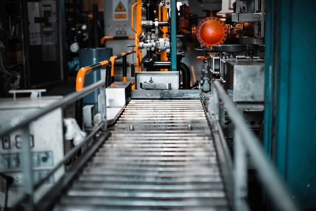 Skrzyżowanie przenośnika rolkowego, zbiornik transportowy przenośnika rolkowego linii produkcyjnej.