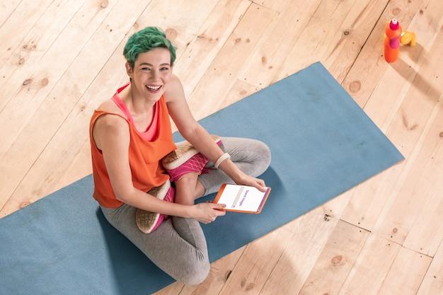 Skrzyżowanymi nogami. promienny zielonooki freelancer siedzący z nogami skrzyżowanymi na niebieskiej macie sportowej i używający tabletu