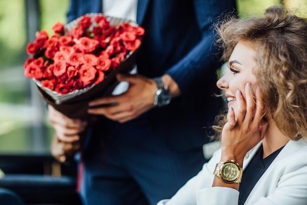 Skup się na dużym czerwonym bukiecie róż, blond kobieta patrzy na prezent, świętuje czas