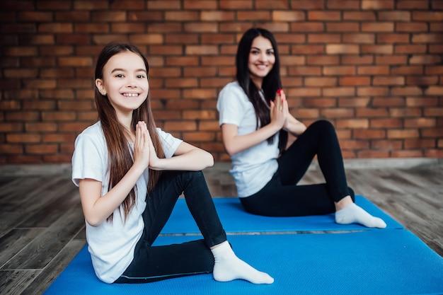 Skup się na uroczej dziewczynce robi medytacji jogi w domu.