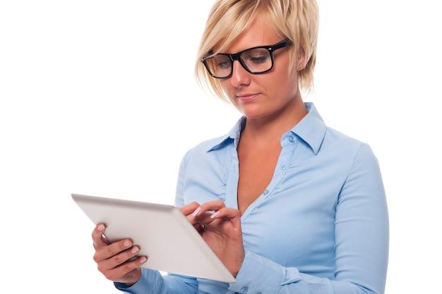 Skup się piękna kobieta podczas pracy na cyfrowym tablecie