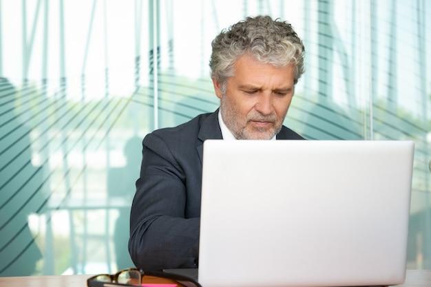 Skupia się dojrzałym wykonawczym pracy na komputerze w biurze, używając białego laptopa przy stole. m