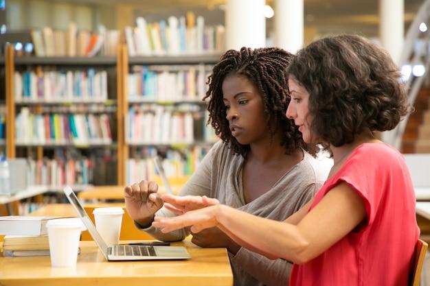 Skupiać się kobiety opowiada i wskazuje przy laptopem przy biblioteką
