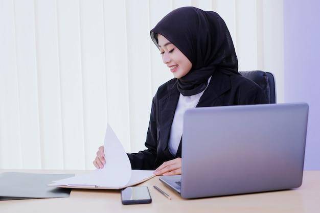 Skupiająca się bizneswoman analizując dokument, trzymając sprawozdanie finansowe w miejscu pracy