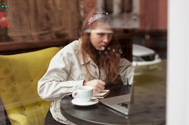 Skupiająca się kobieta patrzeje laptop