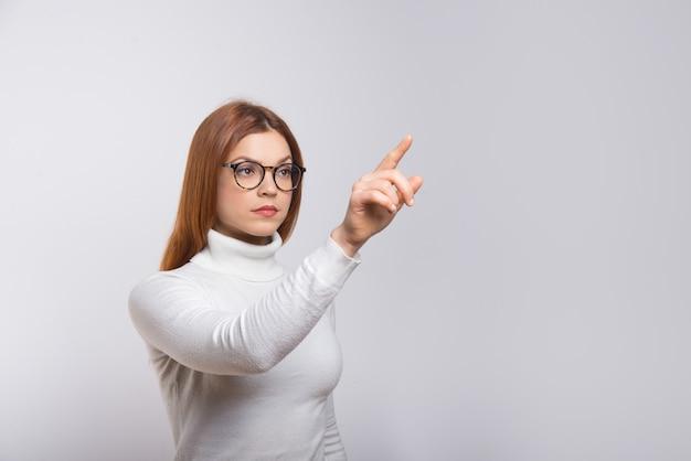Skupiająca się kobieta pcha wirtualnego guzika