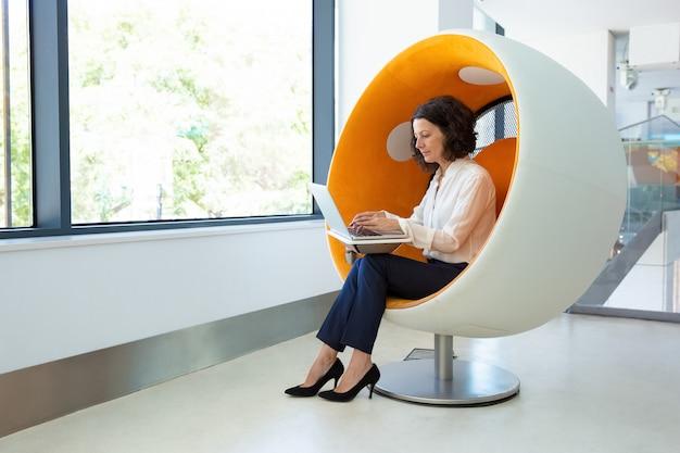 Skupiająca się kobieta używa laptop podczas gdy siedzący w bańczastym krześle