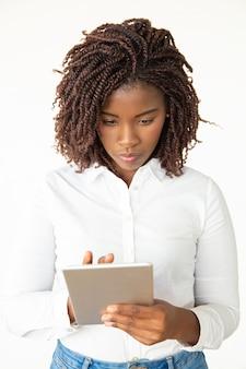 Skupiająca się młoda kobieta z pastylka komputerem osobistym