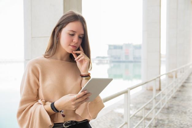 Skupiająca się nastoletnia dziewczyna wyszukuje na pastylka komputerze outdoors