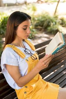 Skupiająca się nastoletnia studencka czytelnicza książka na ławce