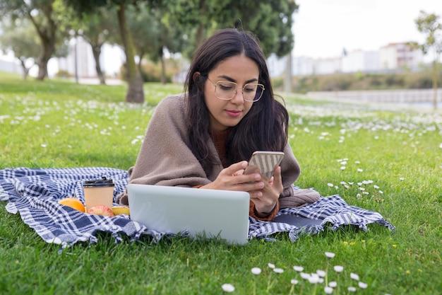 Skupiająca się poważna dziewczyna używa gadżety w parku