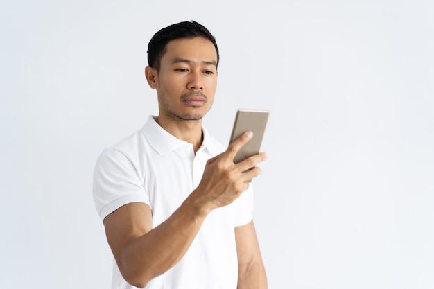 Skupiająca się poważna faceta texting wiadomość