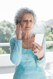 Skupiająca się starsza dama używa telefon i słuchawki