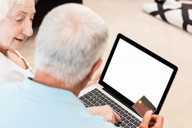 Skupiająca się starsza para używa laptop w domu
