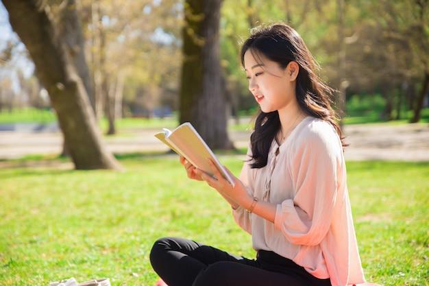 Skupiająca się studencka dziewczyna studiuje jej notatki w parku