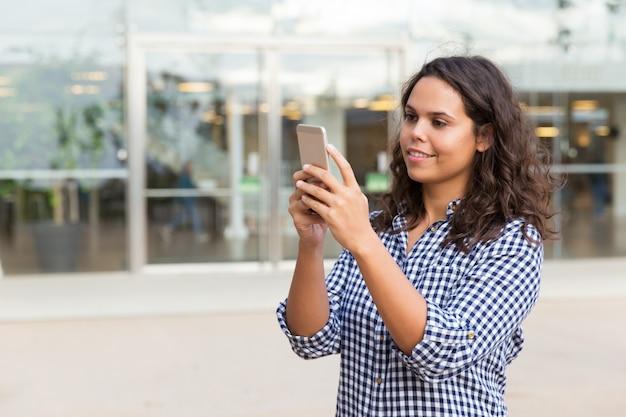 Skupiająca się uśmiechnięta studencka dziewczyna z smartphone konsultuje internet