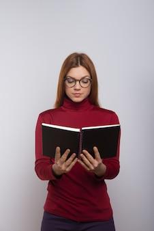 Skupiająca się żeńska studenta collegu czytelnicza książka