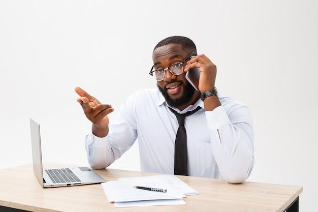 Skupiający się afroamerykański biurowy kierownik siedzi przy biurem z laptopem, czyta znacząco dokumenty z zaintrygowanym wyrażeniem i trzyma głowę z jego ręką