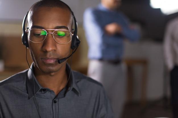 Skupiający się amerykanina afrykańskiego pochodzenia mężczyzna patrzeje w dół z słuchawki