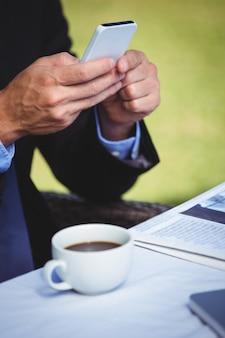 Skupiający się biznesmen patrzeje jego smartphone