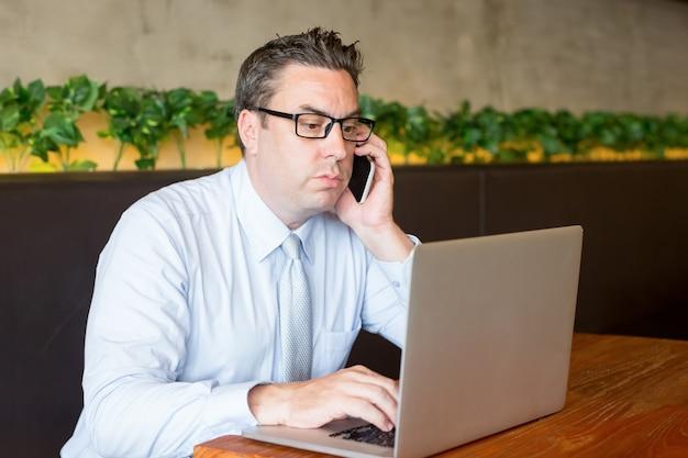 Skupiający się biznesowy mężczyzna pracuje na laptopie w kawiarni