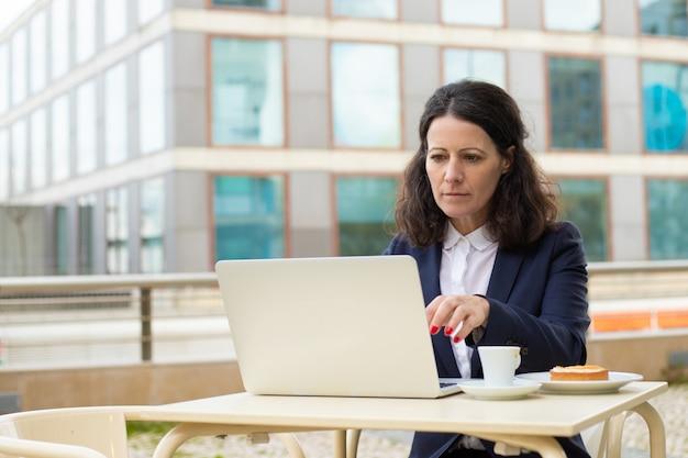 Skupiający się bizneswoman używa laptop w plenerowej kawiarni