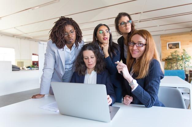 Skupiający się bizneswomany używa laptop