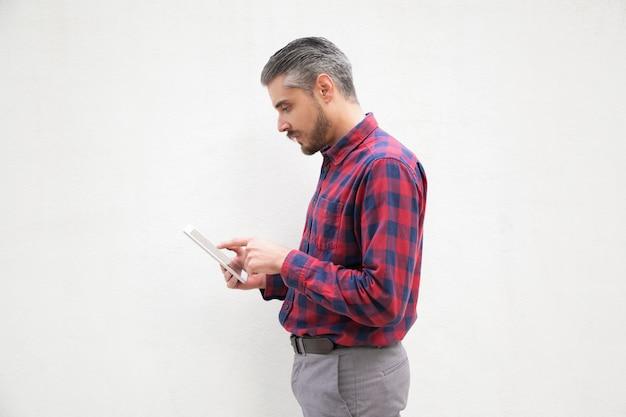 Skupiający się brodaty mężczyzna używa cyfrową pastylkę
