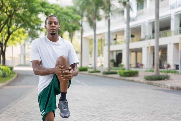 Skupiający się czarny sportowiec rozgrzewkowe nogi przed szkoleniem.
