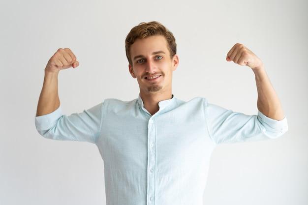 Skupiający się facet w białej przypadkowej koszula pokazuje siła gest.