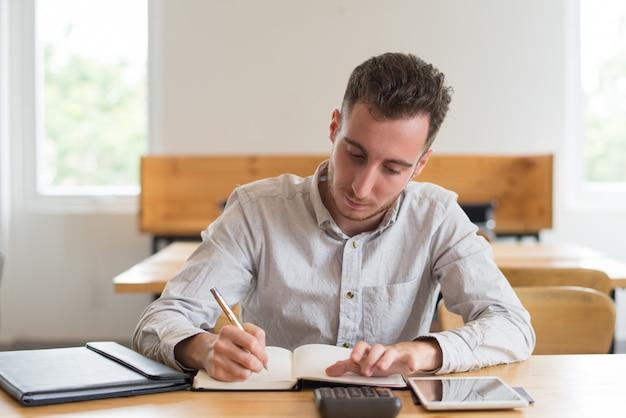 Skupiający się męski uczeń robi pracie domowej przy biurkiem w sala lekcyjnej