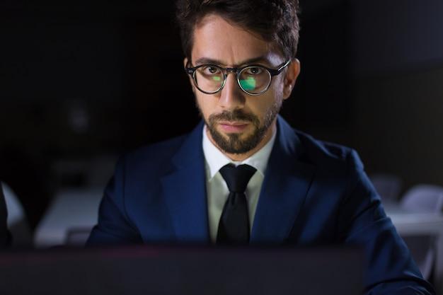 Skupiający się mężczyzna obsiadanie przy stołem z laptopem i patrzeć kamerę